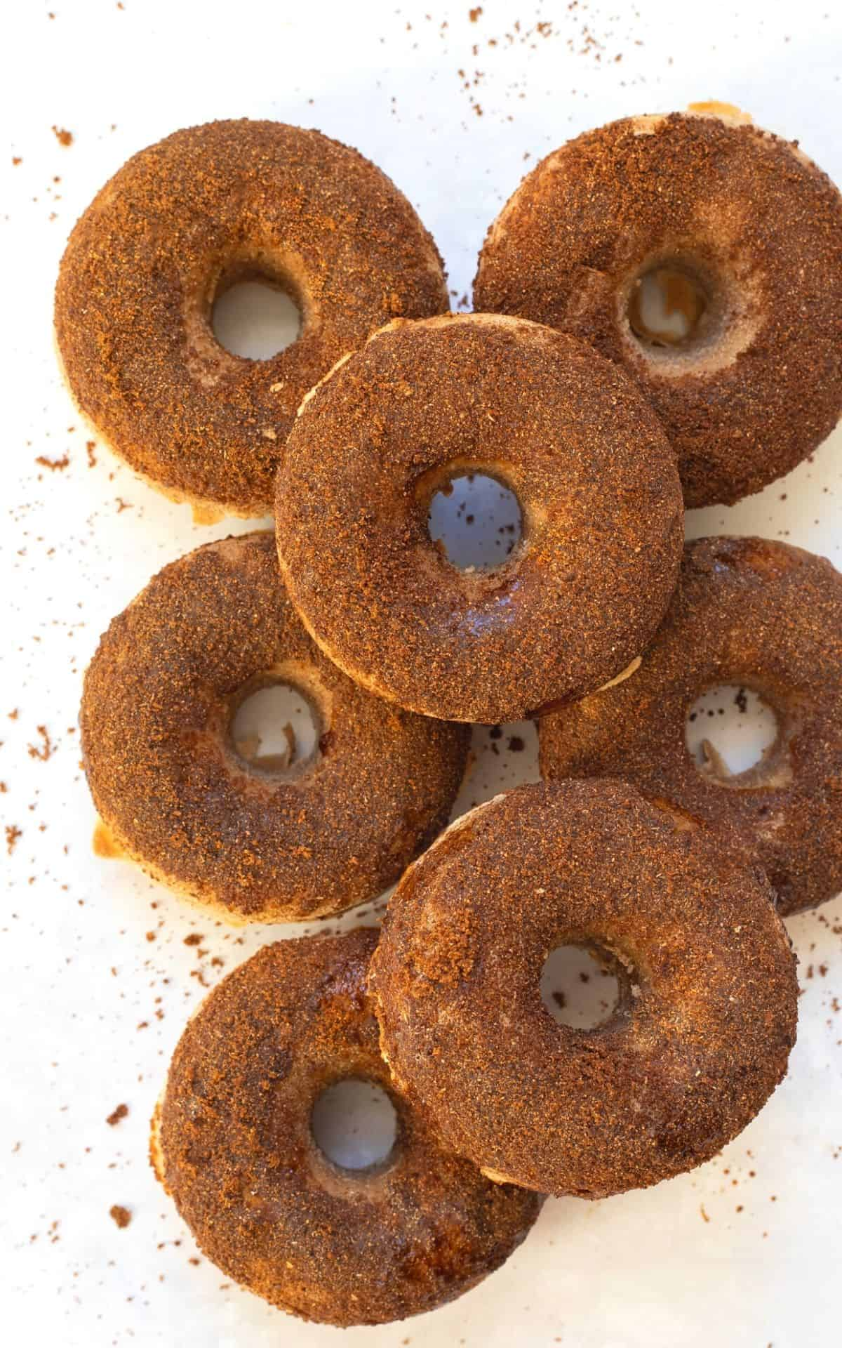 7 cinnamon doughnuts on a white backdrop stacked on top of eachother