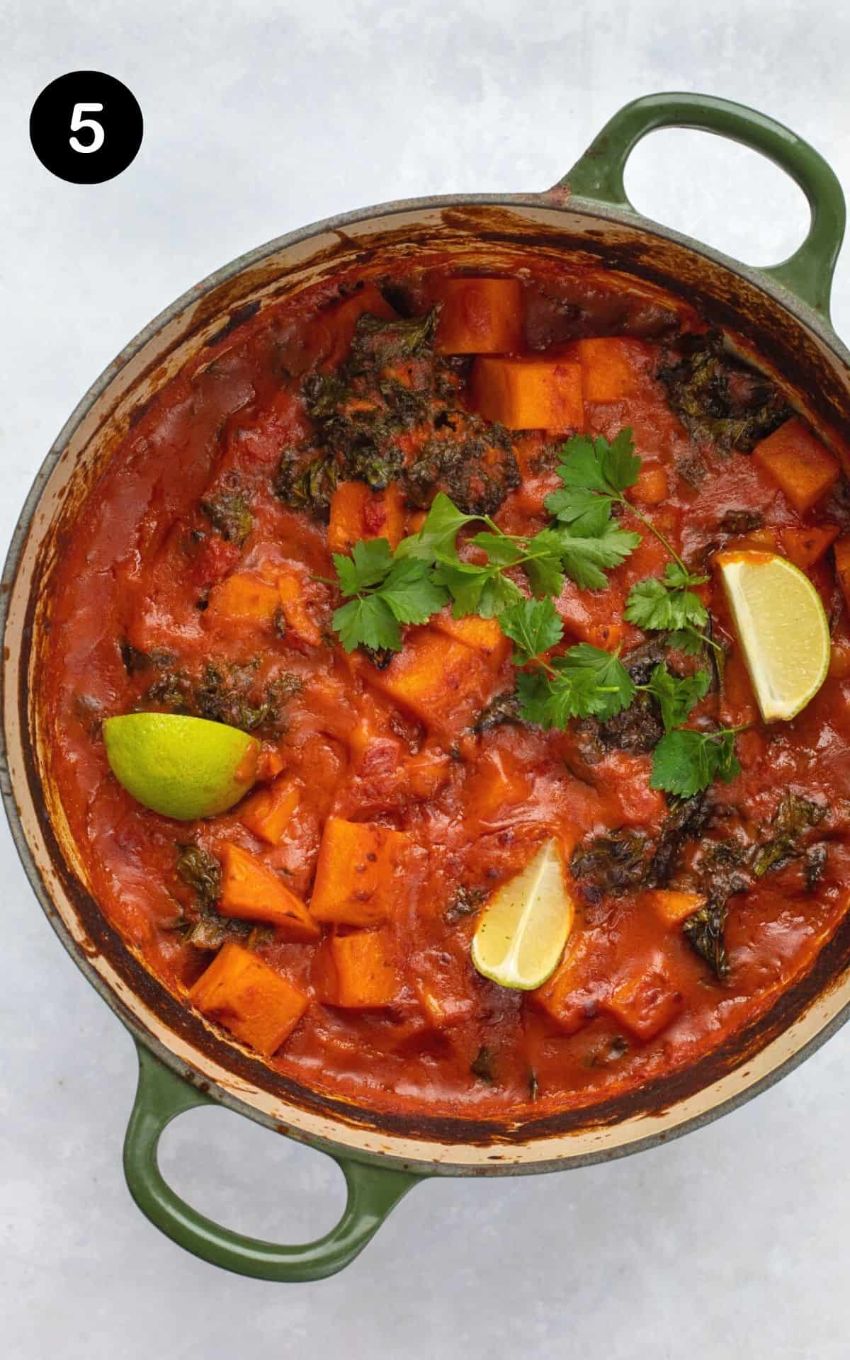 baked sweet potato curry in a pot served with lime and coriander