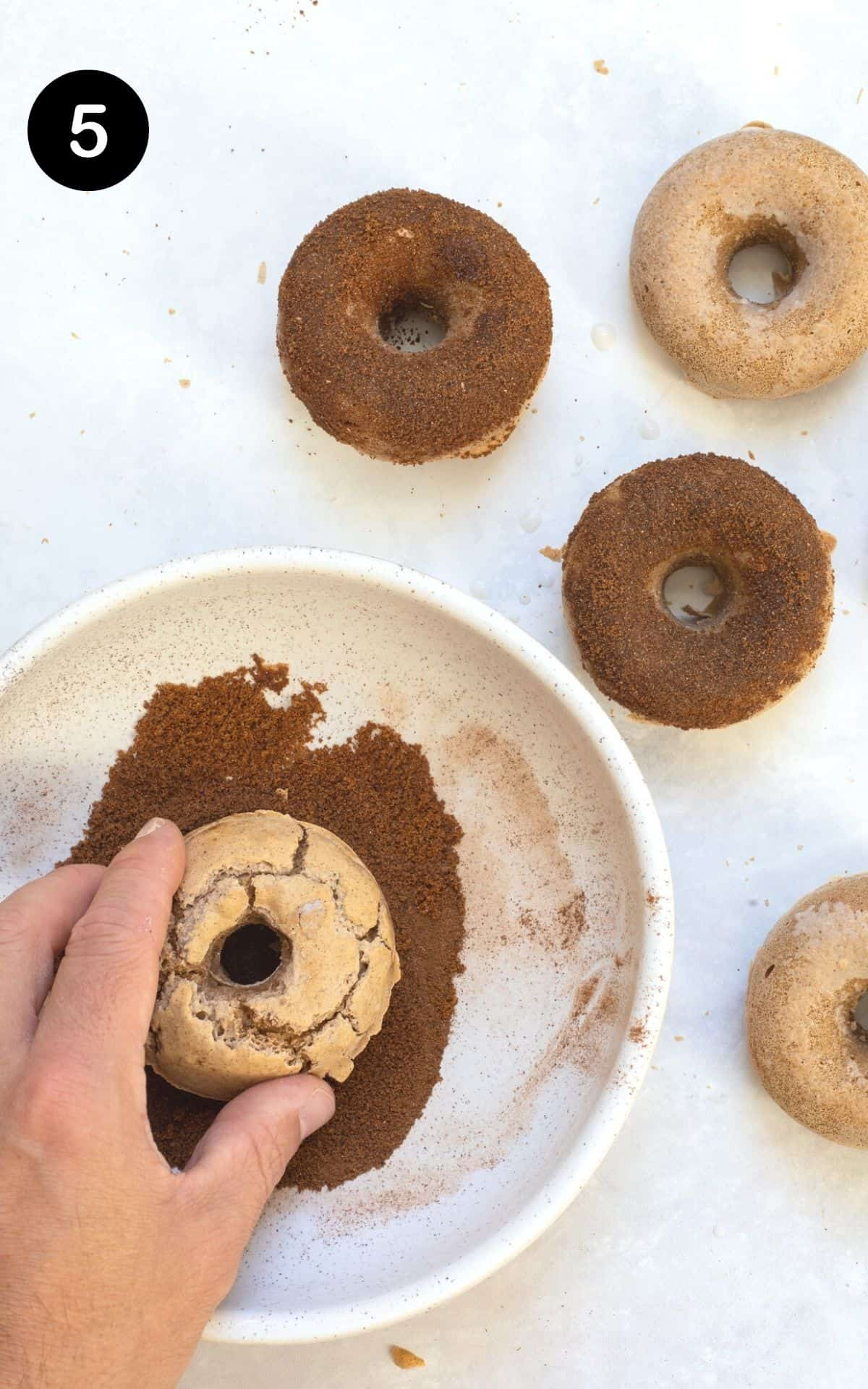 dipping the doughnuts into a bowl with cinnamon sugar
