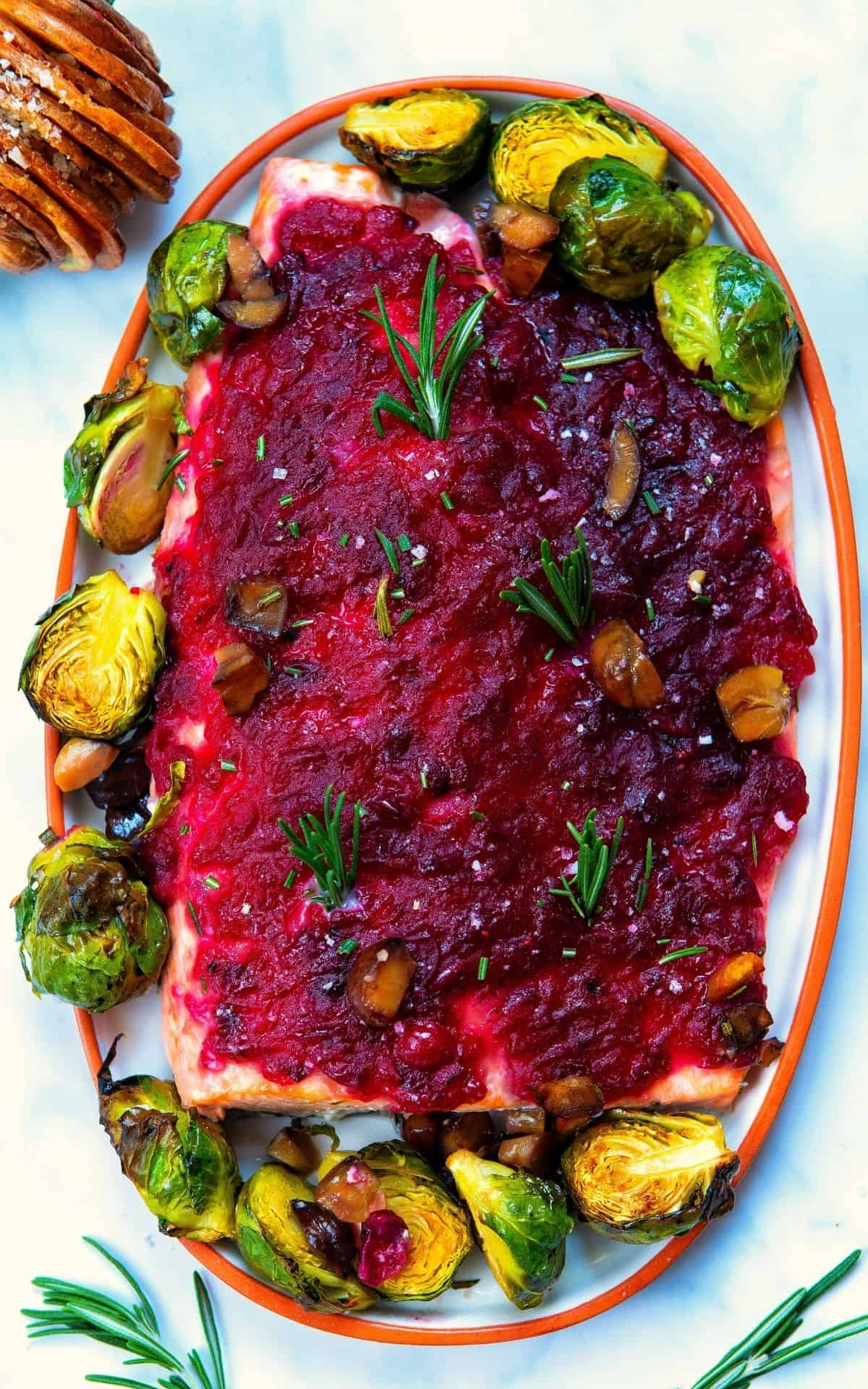 Platter with a large fillet of salmon with baked with cranberry sauce on top and with brussels sprouts around it.
