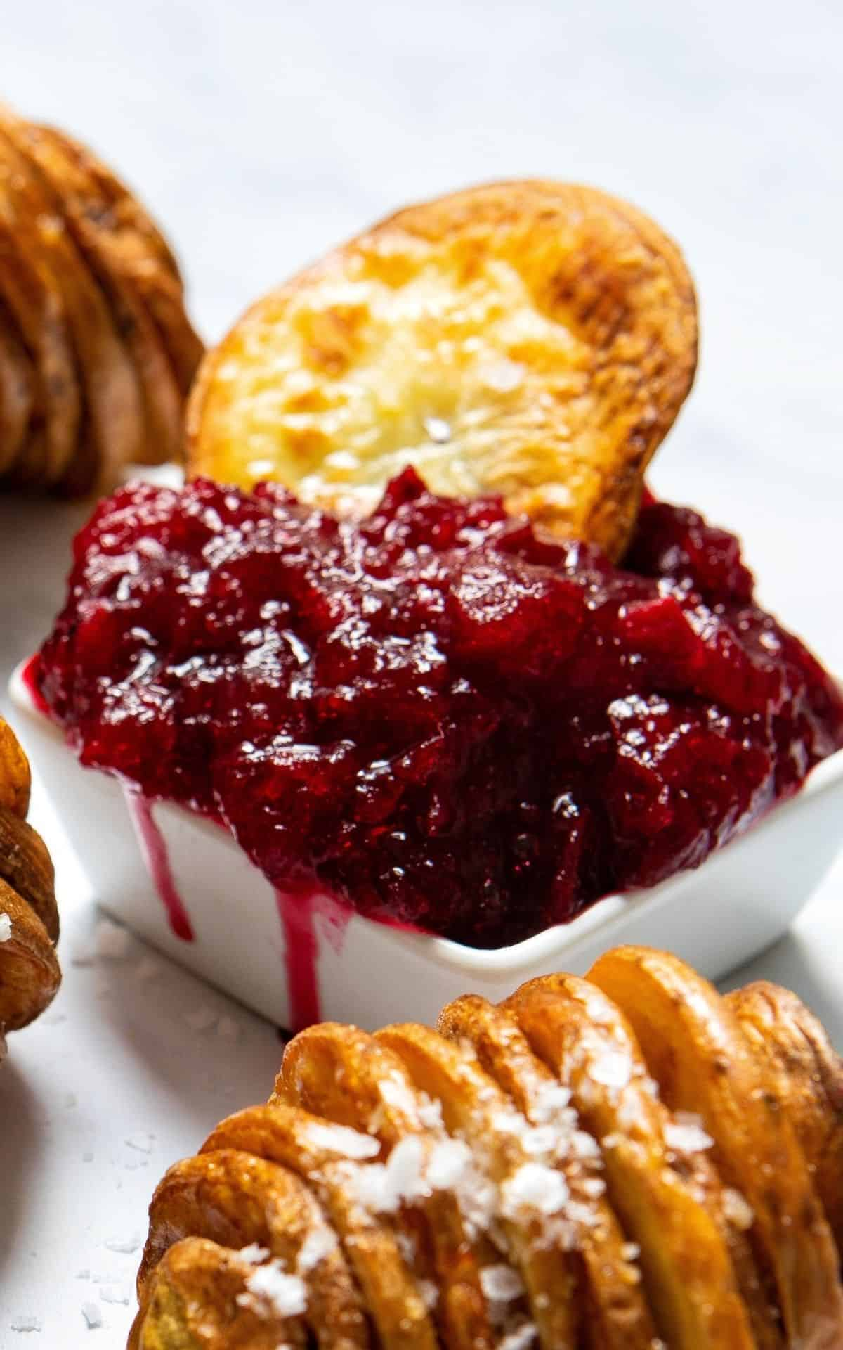 Potato slice dipped in a bowl of homemade sugar-free cranberry sauce.