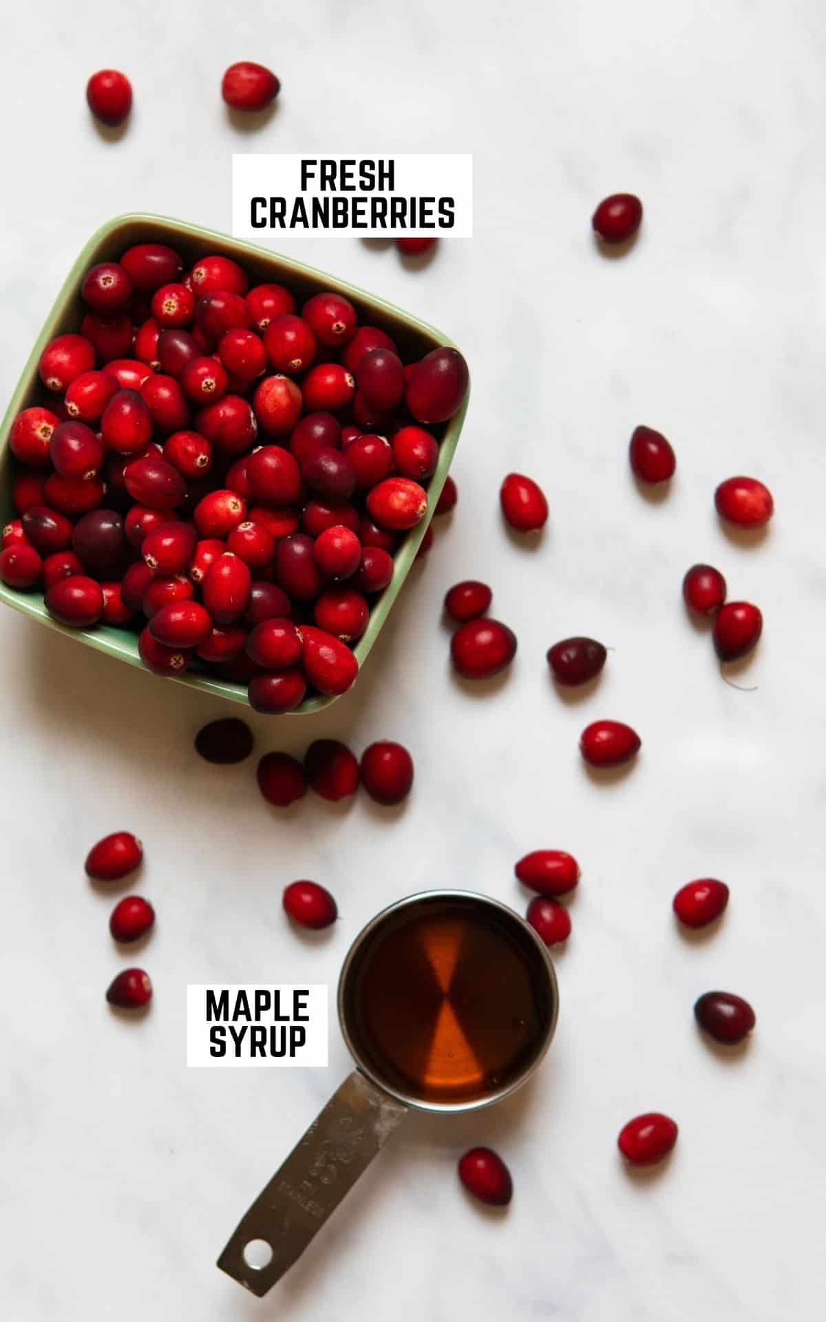 Image of ingredients to make homemade cranberry sauce: fresh cranberries in a bowl and a measuring cup with maple syrup.