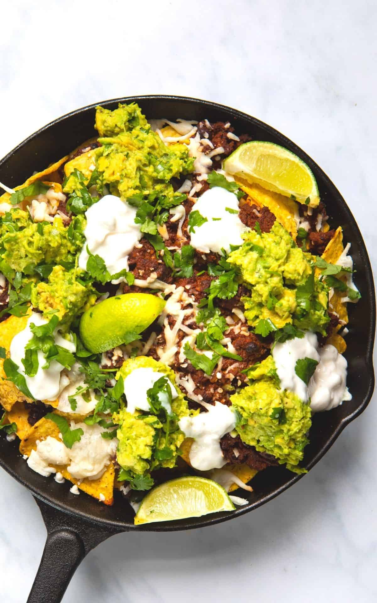 loaded vegan mince nachos in a skillet pan topped with guacamole and cheese