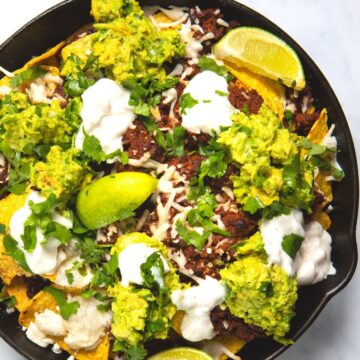 meat-free nachos in a skillet pan topped with guacamole and cheese