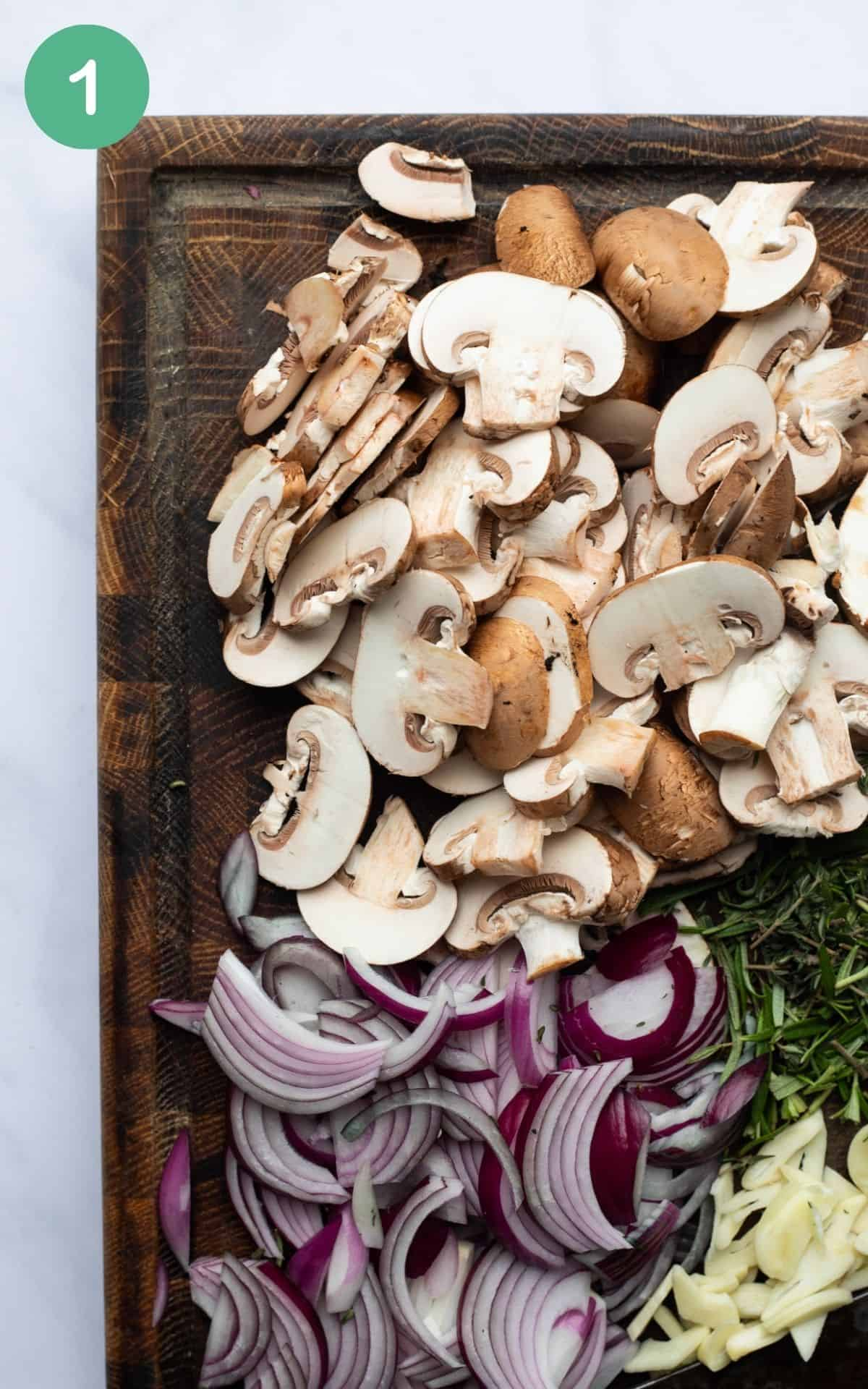 sliced mushrooms, onions, garlic, and herbs on a cutting board