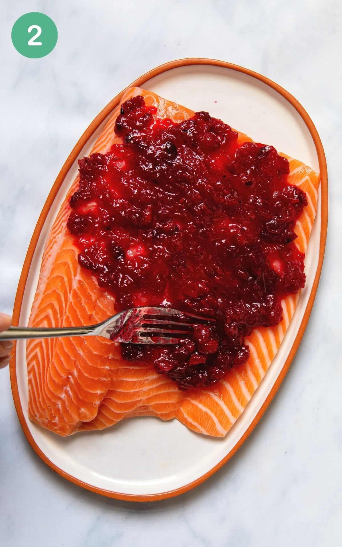Spreading cranberry sauce with a fork onto a salmon fillet before baking.