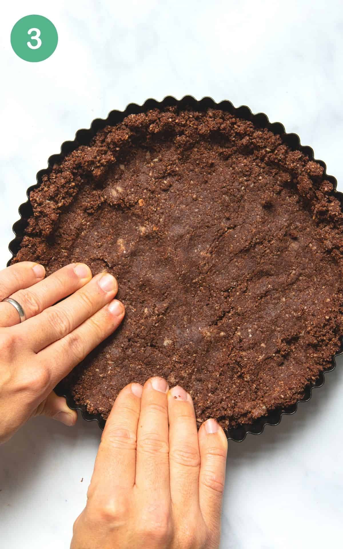 Instructional photo showing the tart crust being pressed into a tart tin.