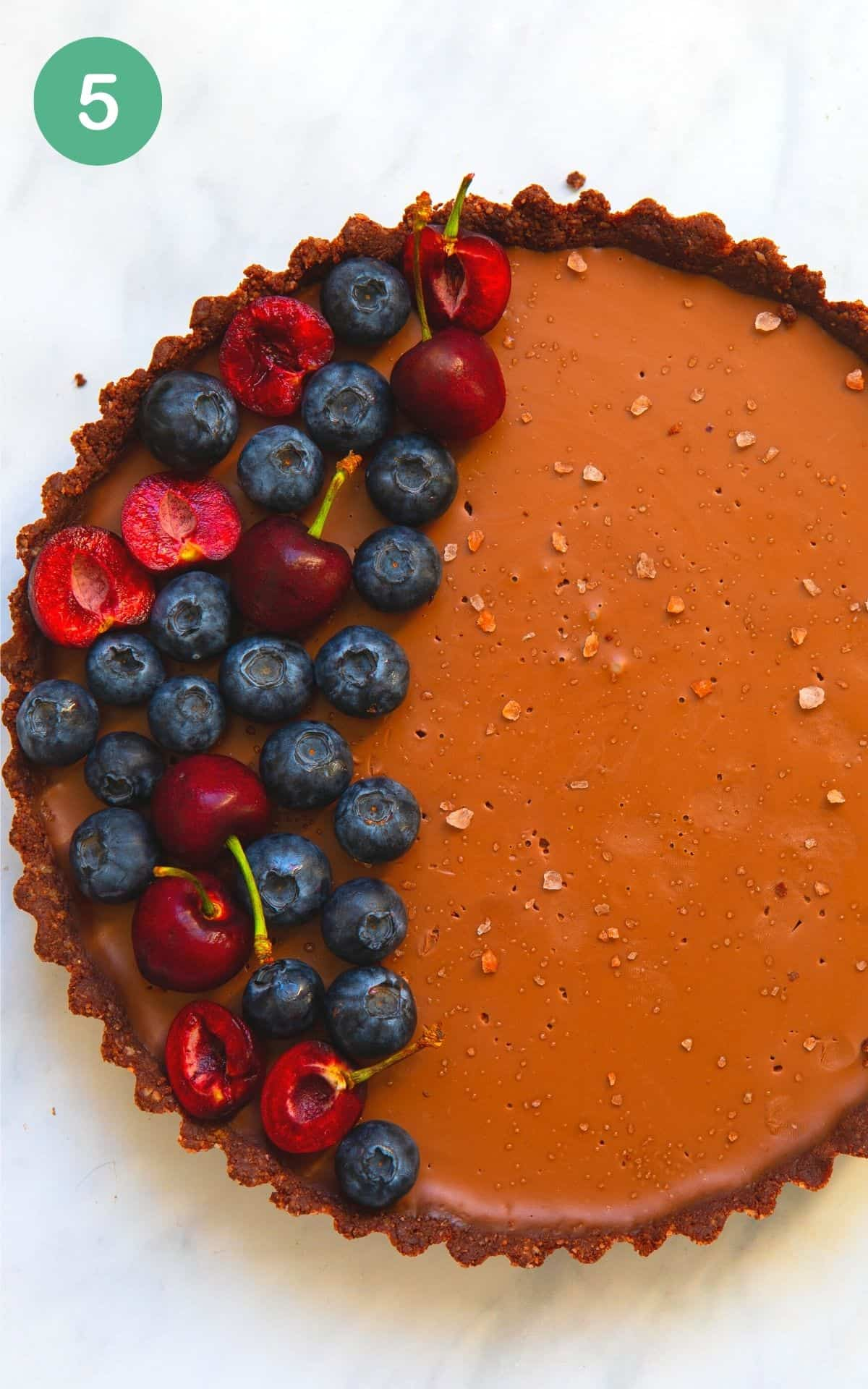 Overhead image of a vegan chocolate tart with fresh berries on top and flakey salts.