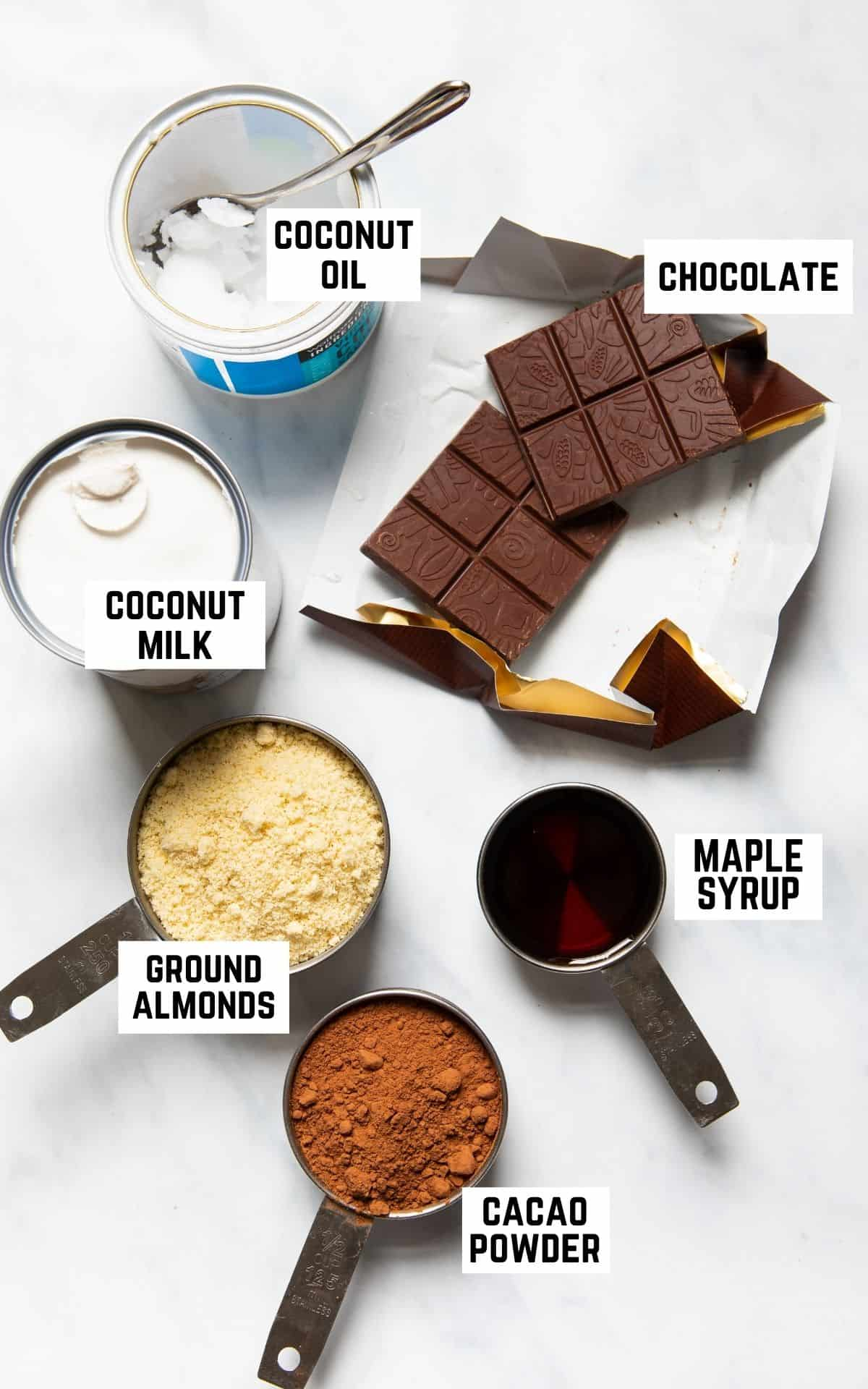 Ingredient flatlay showing coconut oil, chocolate, coconut milk, ground almonds, maple syrup, and cacao powder.
